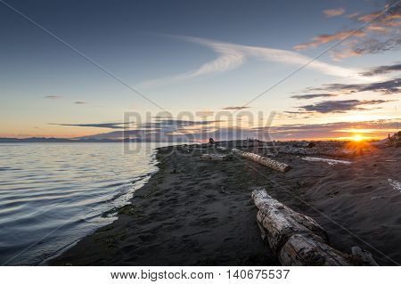Sunset on sea with cloudy sky, rays of light and beach