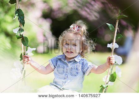 Little cute girl swinging on teeter in summer park, portrait outdoor