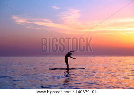 Silhouette of a yoga teacher over sunset background doing asanas, balancing on the sup board, enjoying healthy lifestyle, summer vacation on the beach