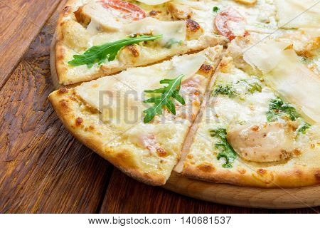 Delicious italian pizza with chicken, parmesan, tomatoes, white sause and fresh arugula - thin pastry crust at wooden background, one piece cut