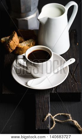 Italian coffee set for breakfast. Cup of hot espresso, creamer with milk, cantucci and moka pot and cookies on dark rustic wooden board over black background, selective focus, vertical composition