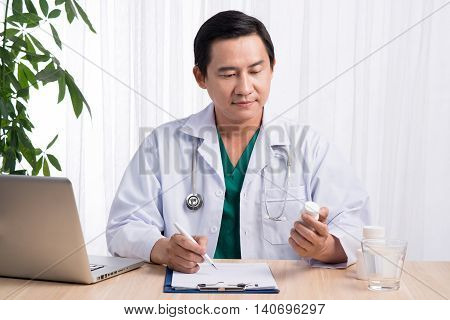 picture of young male asian doctor with jar of capsules in his office