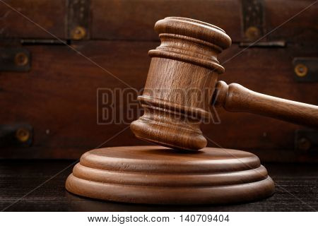 Judge hammer on brown wooden background close up with copy space