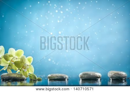 Black massage stones and orchid in blue water background