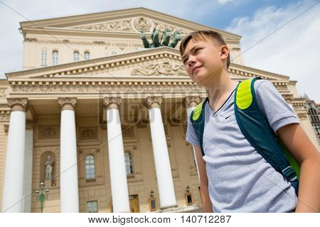 Boy stands in the background of the Bolshoi Theatre, Moscow