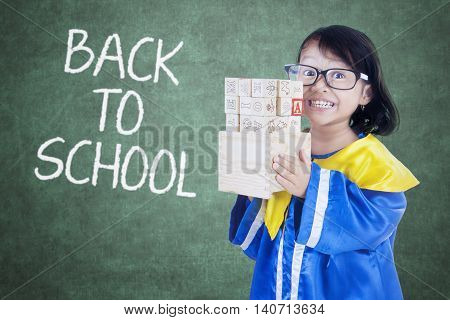 Picture of a female kindergarten student holds letter blocks with text of Back to School on the chalkboard