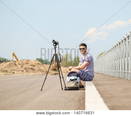 Man with photo camera on tripod taking timelapse photos in the city
