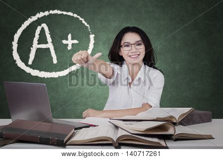 Female high school student showing thumb up with grade A plus on the chalkboard