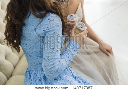 Bride in wedding dress with bridesmaid holding a beautiful blue wedding cupcakes and sitting on sofa