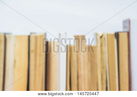 Stack of old books in hard and soft cover blurred background. Blur books of Background