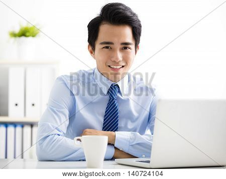 smiling young business man working on laptop