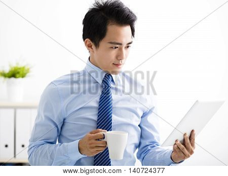 smiling young business man reading the tablet