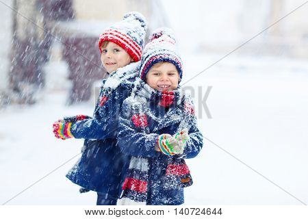 Two little kid boys in colorful clothes, outdoors during snowfall. Active outoors leisure with children in winter on cold snowy days. Happy siblings having fun with snow
