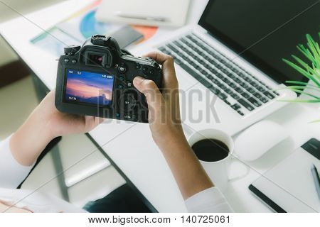 photographer holding camera checking photo on her desk workspace