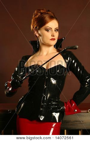 Powerful dominatrix type redhead woman wearing a latex jacket and skirt holding a riding crop in a strong stance. poster