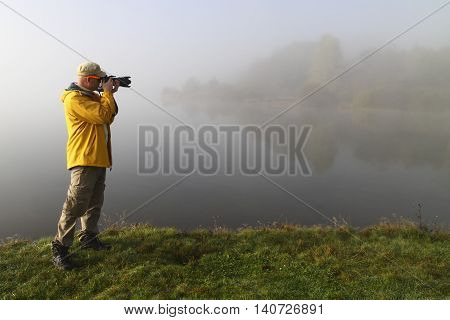 Nature photographer in yellow jacket in action