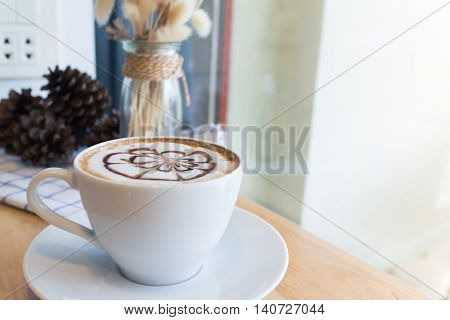 hot coffee with foam milk art in afternoon break.(selective focus vintage effect)