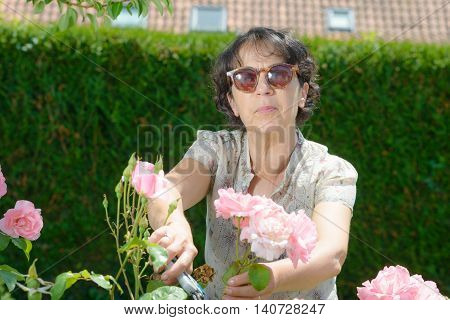 a middle-aged woman with sun glasses in the garden