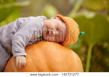 sweet baby with pumpkin hat sleeping on big orange pumpkin