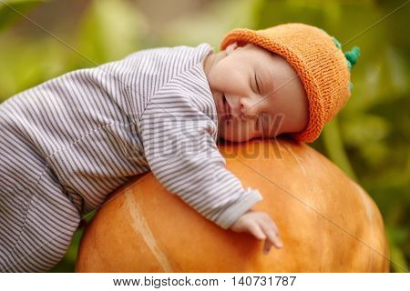 sweet baby with pumpkin hat sleeping on big orange pumpkin