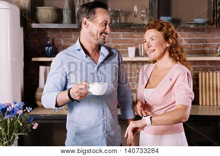 We have to go. Demanding woman pointing on the watch and looking at her husband who holding a cup of coffee