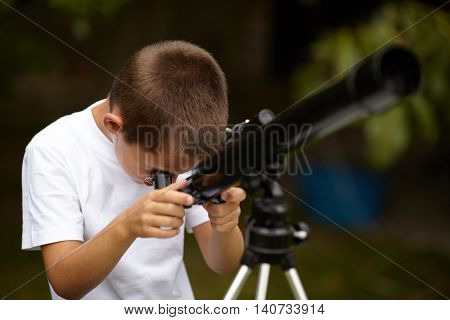 photo of happy little boy with telescope