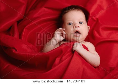 photo of beautiful baby lying on red silk background