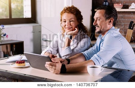 Thats pretty good. Beautiful woman talking with a handsome man while sitting in the kitchen and looking at the tablet