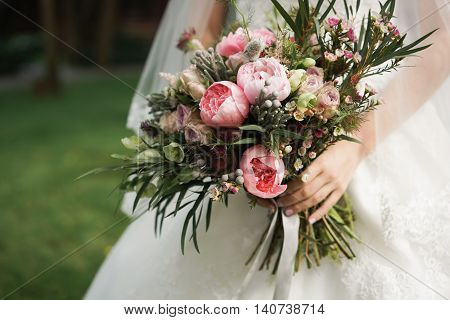 Bride in a white dress holding a bouquet of purple flowers and greenery on the background of green grass.