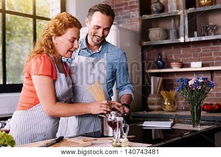 I am starving. Good looking woman and bearded mature man cooking a pasta together in a stylish kitchen