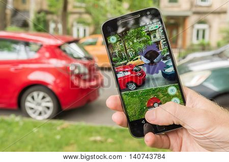 Montreal CA - July 28 2016: Closeup of a man playing Pokemon Go on a smart phone. Pokemon Go is a virtual reality game released in July 2016.
