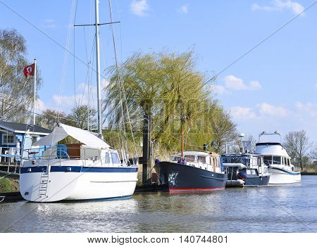 Anchored boats at a pier. River with anchored ailing ship and motorboats. Water reflections and blue sky on a sunny day in the wetland.