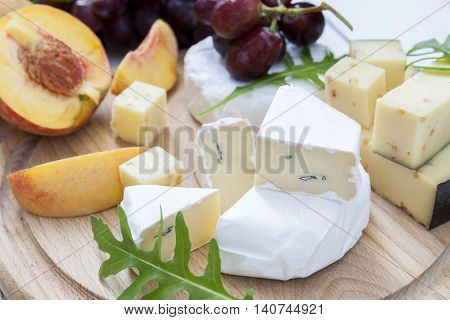 Different Delicious Cheeses And Fruits On Wooden Round Board