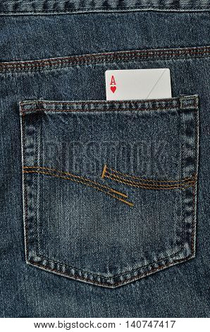 An ace of hearts in the back pocket of a denim jeans pants