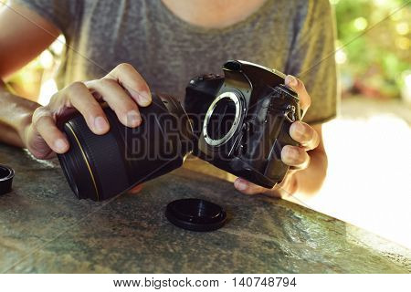 closeup of a young caucasian man taking out the lens of his reflex camera outdoors