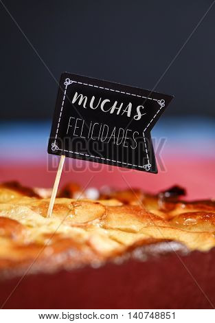 closeup of a black flag-shaped signboard with the text muchas felicidades, congratulations in Spanish, topping a cake, in occasion of a birthday, an anniversary, a wedding or a birth
