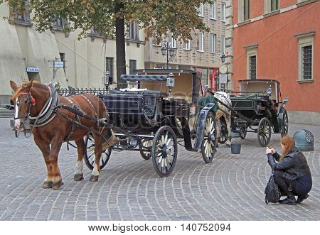 Warsaw, Poland - October 25, 2015: woman are shooting horse carriage at main square in Warsaw, Poland