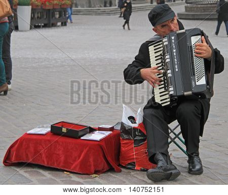 Warsaw, Poland - October 25, 2015: man are playing the accordion at the square nearly Royal Castle in Warsaw