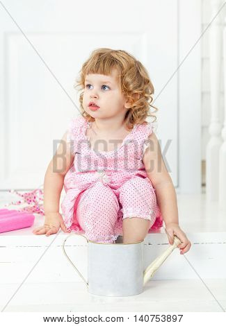 Little cute curly girl in a pink dress with polka dots sitting on the white porch and bathing her feet in the childish watering. Provence style