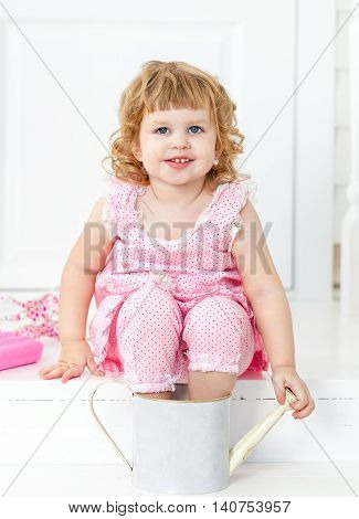 Little cute curly girl in a pink dress with polka dots smiling sitting on the white porch and bathing her feet in the childish watering. Provence style