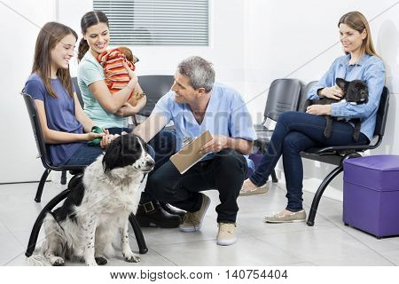 Male Nurse Crouching By Pets And Owners In Waiting Area