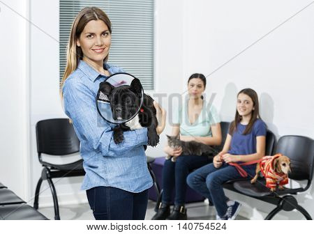 Woman Carrying Bulldog With Cone In Clinic