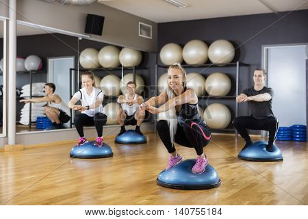 Woman Doing Squatting Exercise On Bosu Ball With Friends