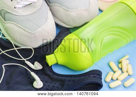 Bottle , sneakers , top headphones,vitamins running concept