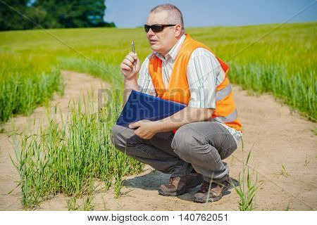 Farmer thinks at cereals field in summer day