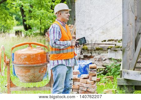 Construction worker using tablet PC near concrete mixer