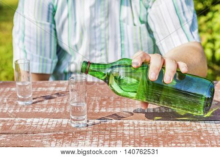 Man poured glass of alcohol in summer day