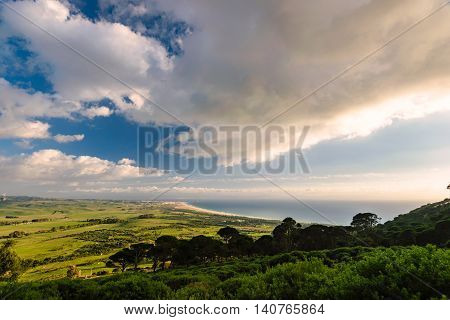 Awesome view over the outback of Tarifa and the Strait of Gibraltar with beautiful weather with blue sky, trees and some clouds.