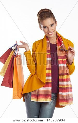 Woman wearing autumn overcoat and scarf  holding shopping bag.