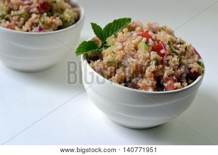 Tabouleh in a white bowl on a white background: Served garnished with a sprig of mint.